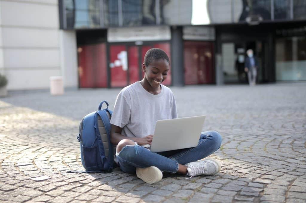 Femme assise en tailleur sur le sol avec son ordinateur ouvert