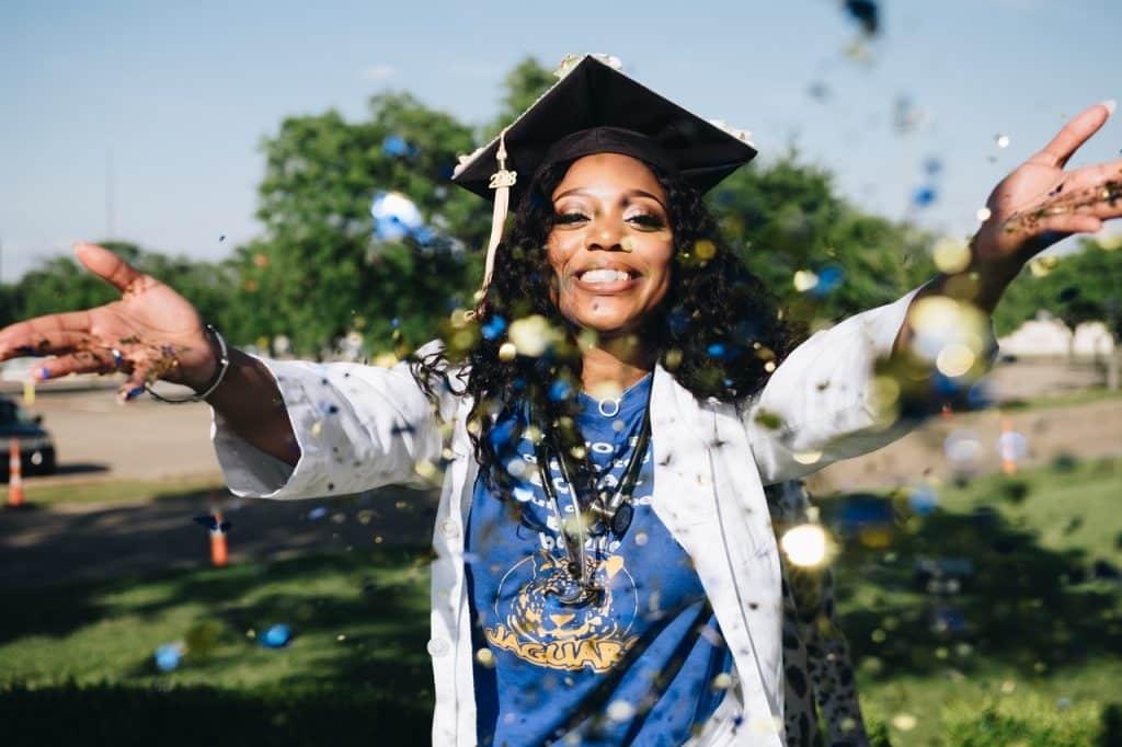 Femme venant de recevoir son diplôme, lançant confettis