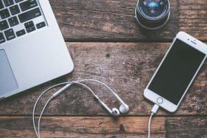 iPhone et Macbook, posé sur un bureau avec des écouteurs