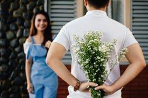 Homme tenant des fleurs dans son dos, voulant les offrir à une femme pour un rendez-vous