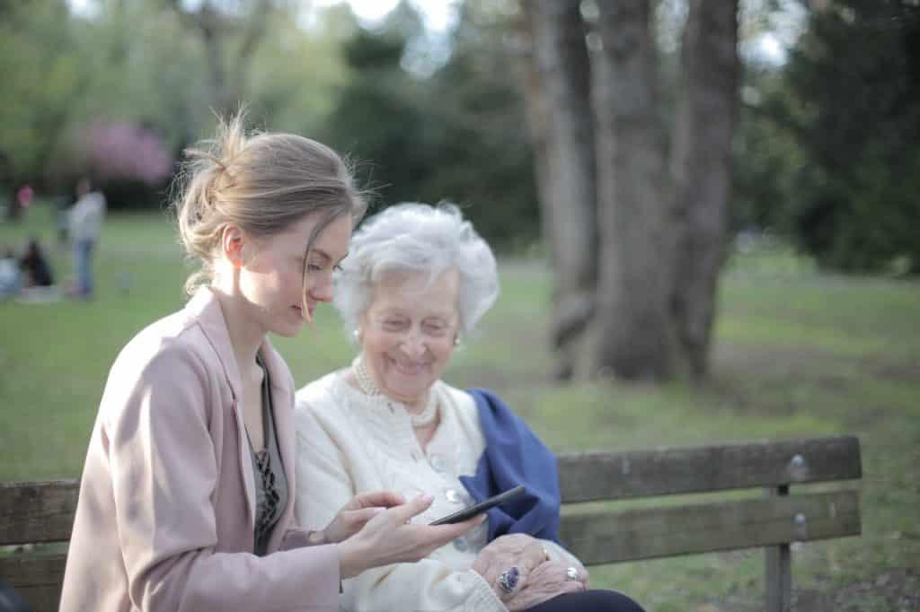 Senior sur un banc avec une femme jeune
